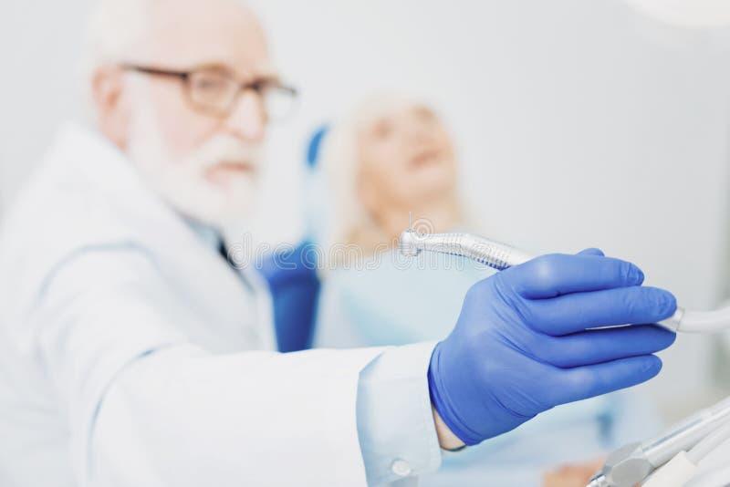 Dentista maschio messo a fuoco che prende strumento immagine stock