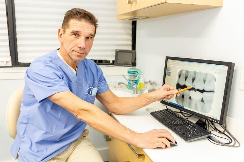 Dentista maschio professionista che sorride alla macchina fotografica in ufficio fotografia stock