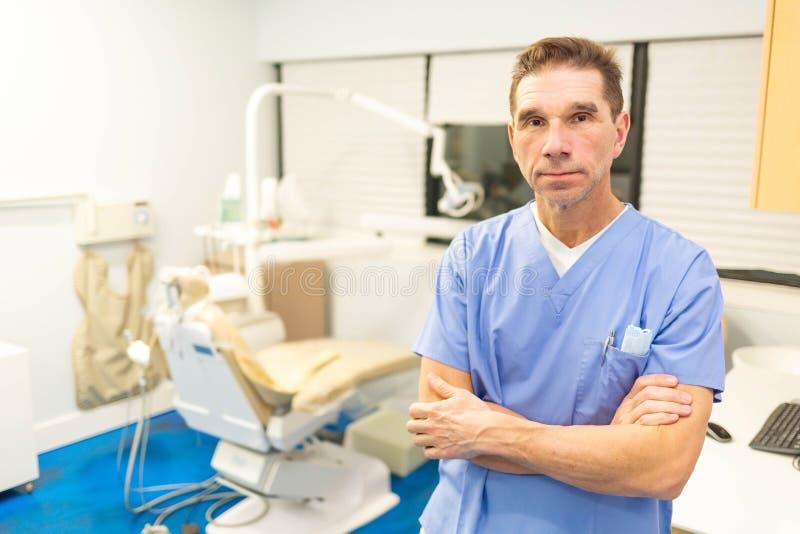 Dentista maschio professionista che sorride alla macchina fotografica in ufficio immagine stock