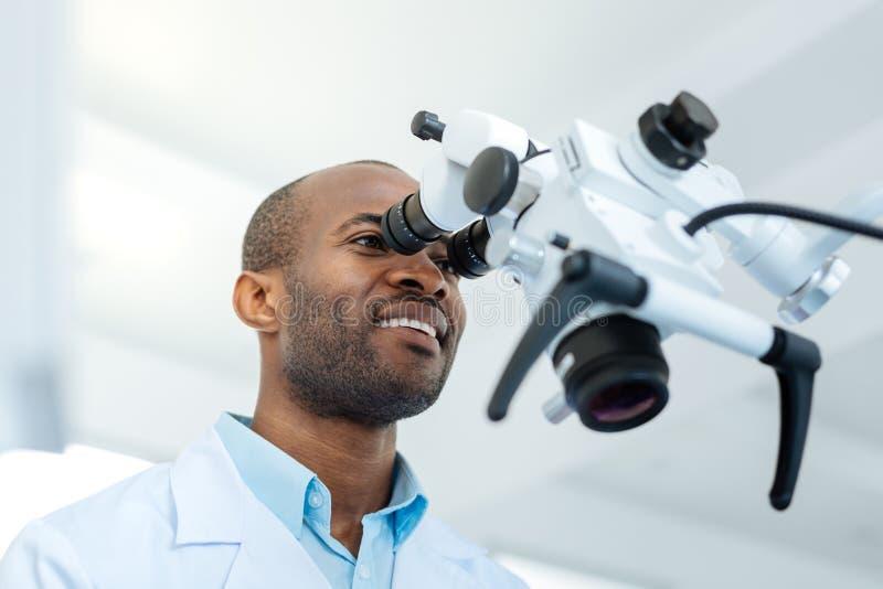 Dentista masculino alegre que olha na lente do microscópio imagens de stock