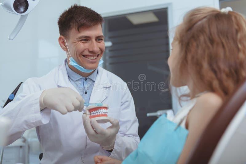Dentista masculino considerável que trabalha em sua clínica fotos de stock