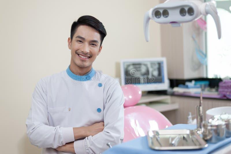 Dentista masculino que cruza a clínica dental de Armin imagem de stock