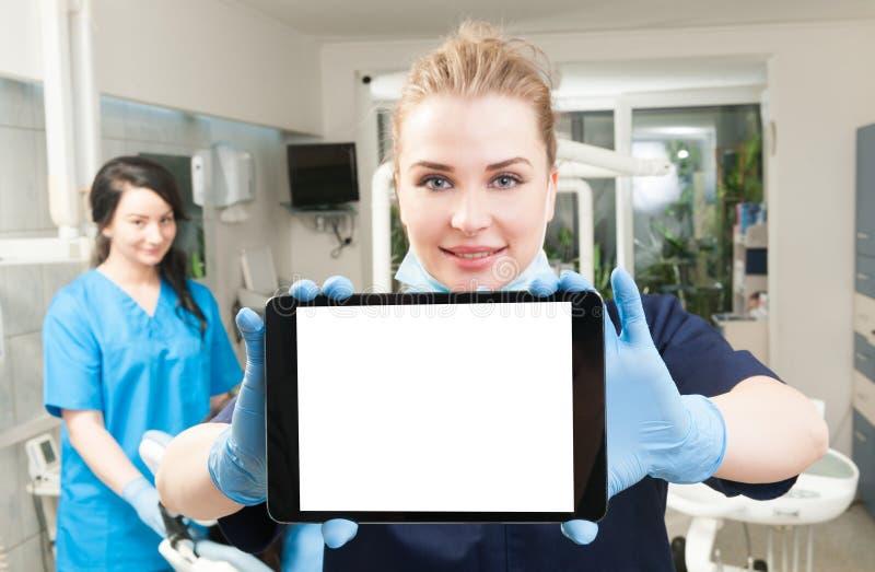 Dentista novo que usa a tabuleta moderna com o assistente nela para trás imagem de stock