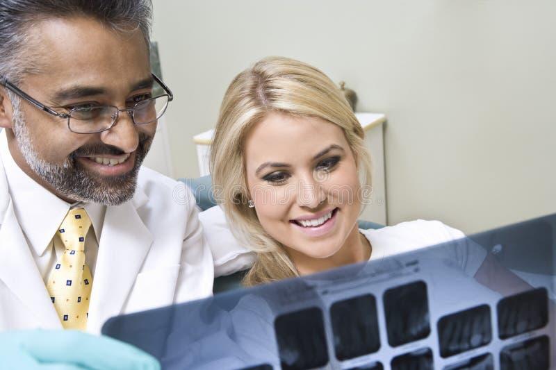 Dentista And Patient Looking ai raggi x fotografie stock