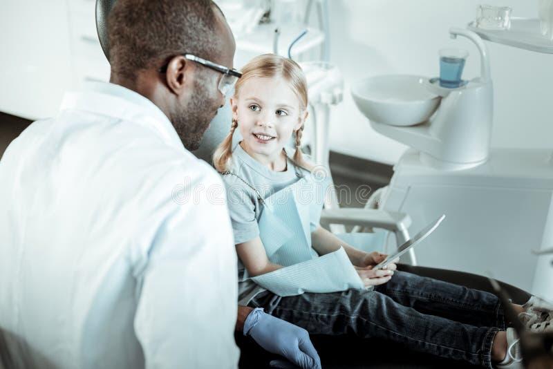 Dentista profesional agradable que habla con su paciente lindo joven imagenes de archivo