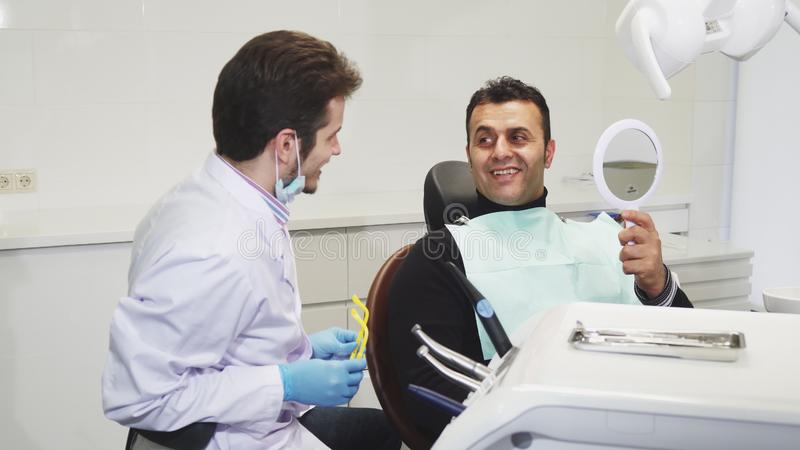 Dentista profissional que dá um espelho a seu paciente após o tratamento dental imagens de stock royalty free
