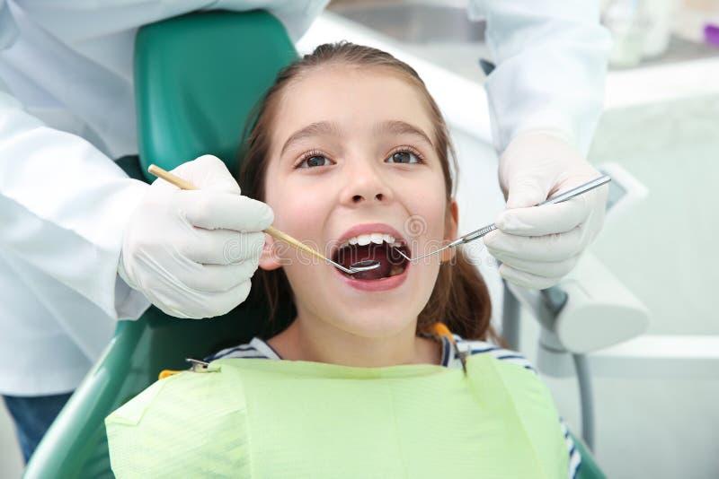 Dentista profissional que trabalha com pouco paciente na clínica foto de stock royalty free