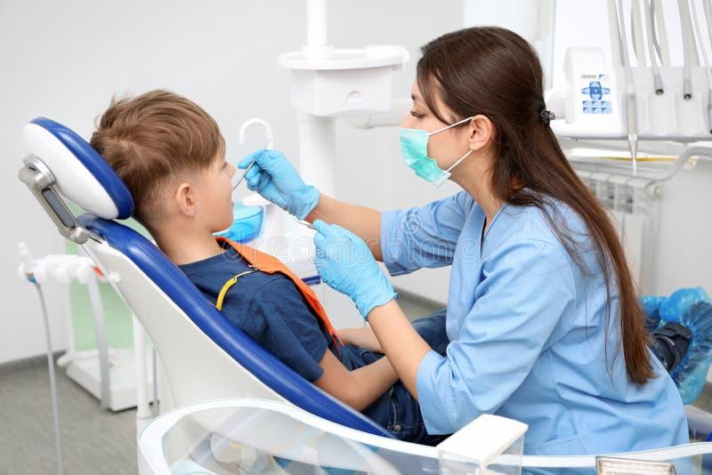 Dentista profissional que trabalha com rapaz pequeno dentro foto de stock royalty free