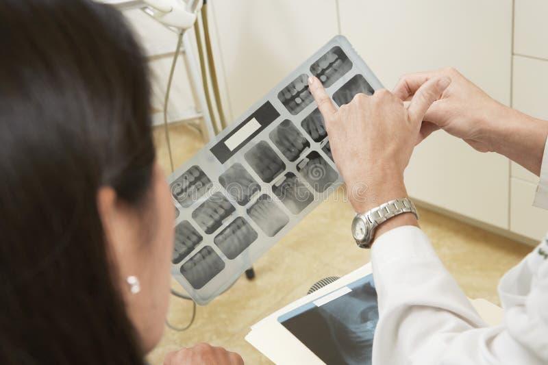 Dentista que aponta para uma cavidade no relatório do raio X foto de stock