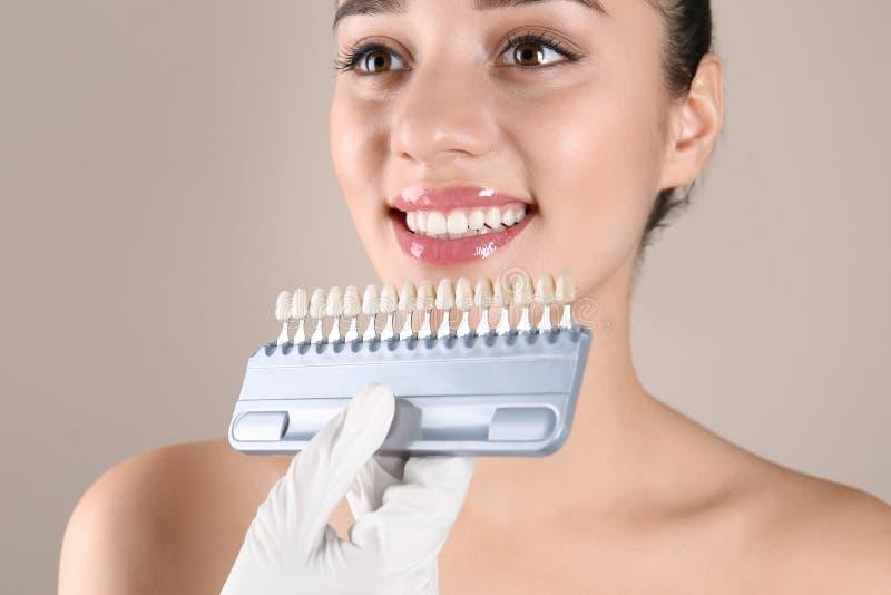 Dentista que comprueba el color de los dientes de la mujer joven imagenes de archivo