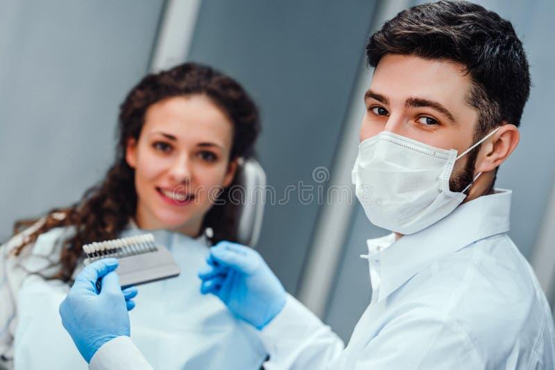 Dentista que comprueba y que selecciona color de los dientes de la mujer joven que miran el cierre de la cámara encima de la visi fotografía de archivo