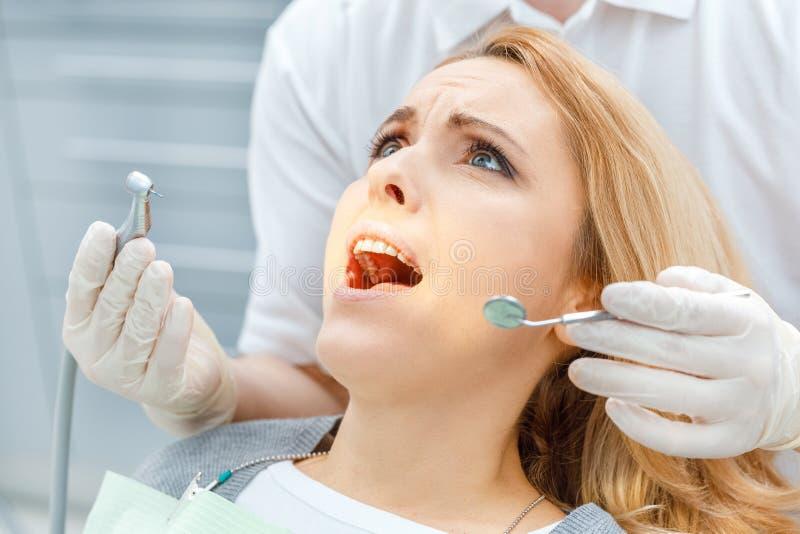 Dentista que cura al paciente asustado que mira para arriba foto de archivo libre de regalías