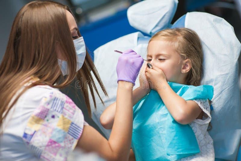 Dentista que cura um paciente da criança no escritório dental imagens de stock