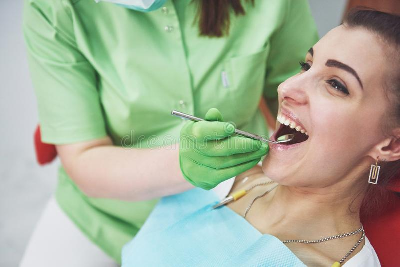 Dentista que cura a un paciente femenino en la estomatología Concepto de la prevención temprana y de la higiene oral imagenes de archivo