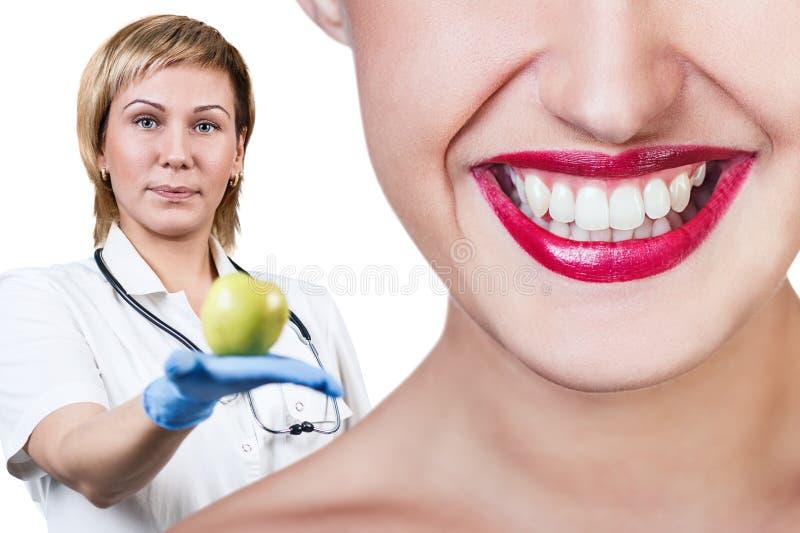 Dentista que da la fruta de la manzana a la mujer joven foto de archivo libre de regalías