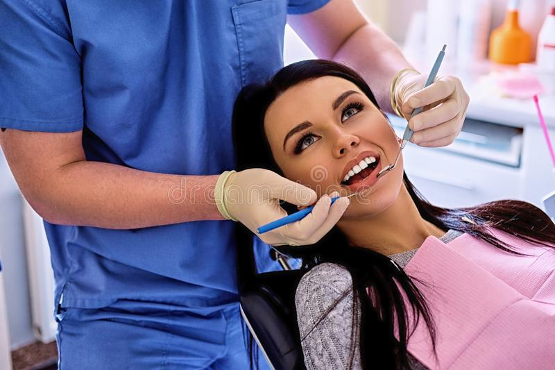 Dentista que examina los dientes femeninos del ` s en odontología imagen de archivo libre de regalías