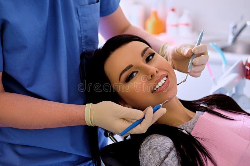 Dentista que examina los dientes femeninos del ` s en odontología foto de archivo libre de regalías