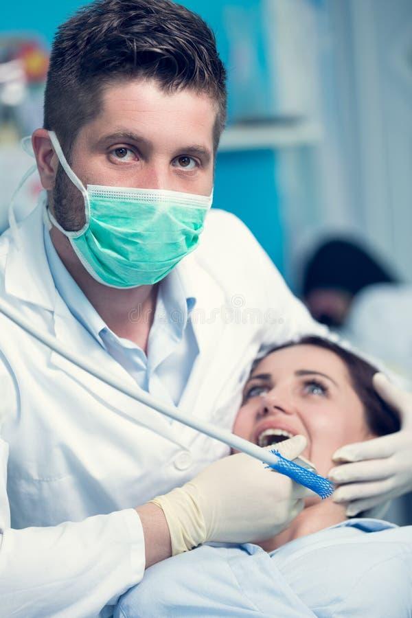 Dentista que examina os dentes pacientes com um espelho de boca fotografia de stock royalty free