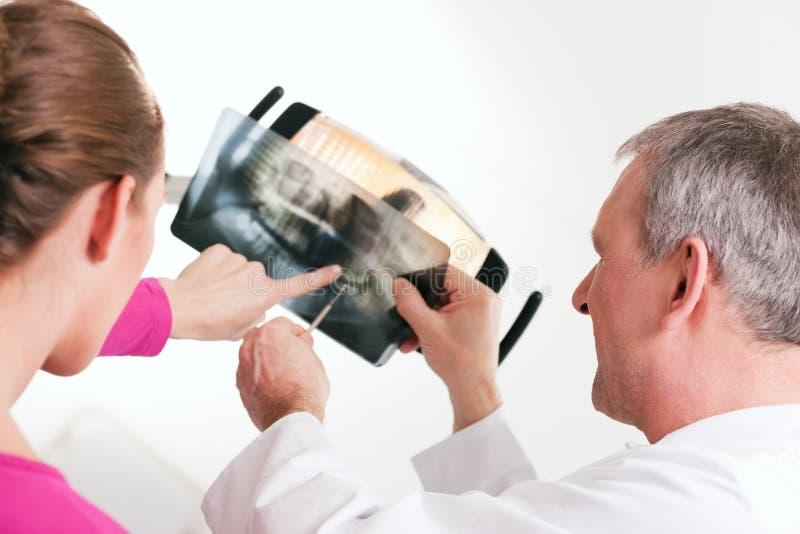 Dentista que explica la radiografía al paciente foto de archivo libre de regalías