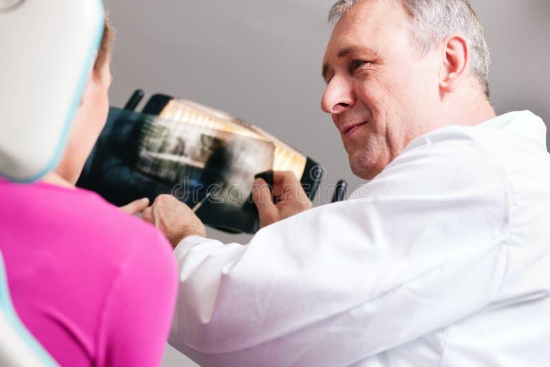 Dentista que explica la radiografía al paciente imágenes de archivo libres de regalías