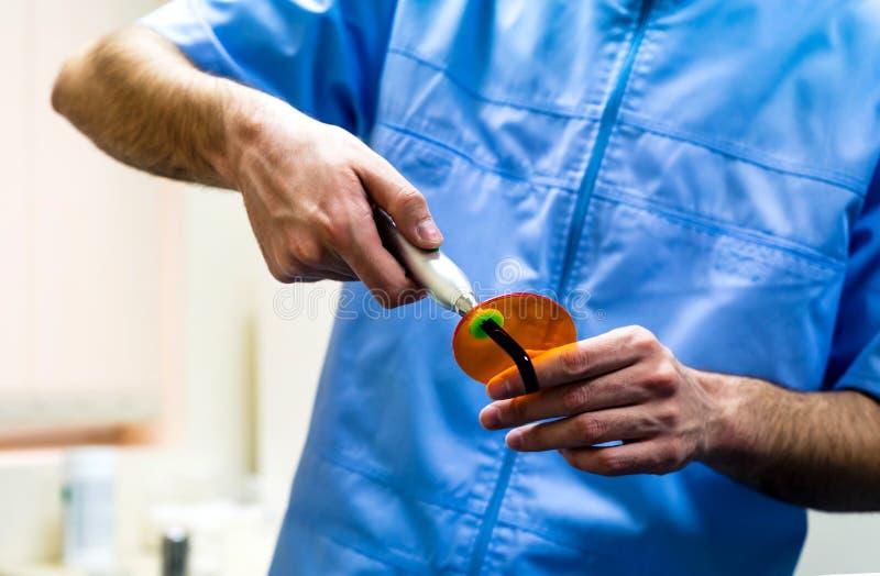 Dentista que guarda um close up de cura dental da lâmpada foto de stock