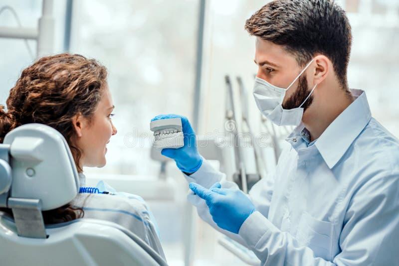 Dentista que habla con su paciente que muestra su molde dental Vista lateral foto de archivo libre de regalías