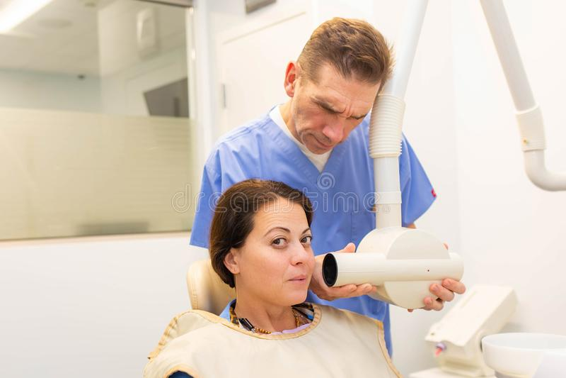 Dentista que lleva una radiografía de los dientes un paciente fotos de archivo libres de regalías