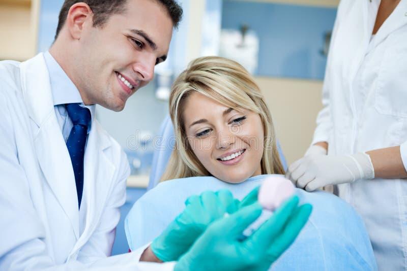 Dentista que muestra la muestra de los dientes fotografía de archivo