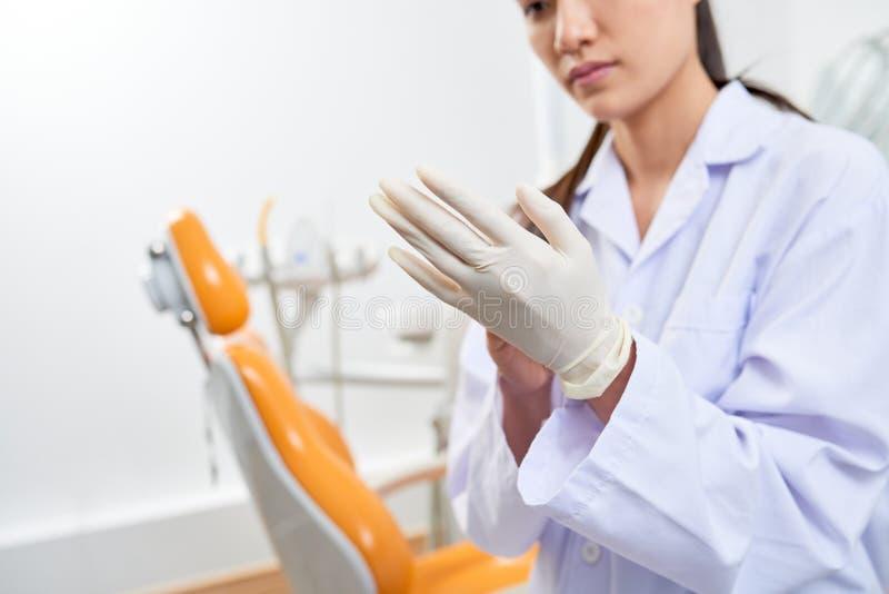 Dentista que põe sobre luvas do látex foto de stock