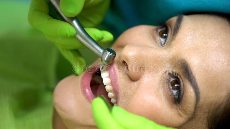 Dentista que prepara-se para furar o incisivo central que prepara o dente para a colocação do vedador foto de stock royalty free
