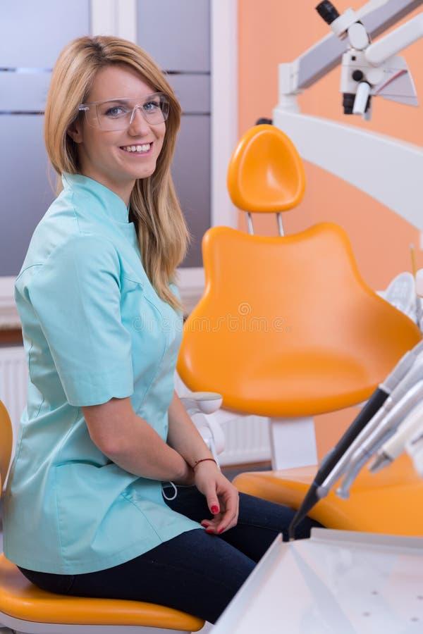 Dentista que se sienta en taburete dental fotografía de archivo