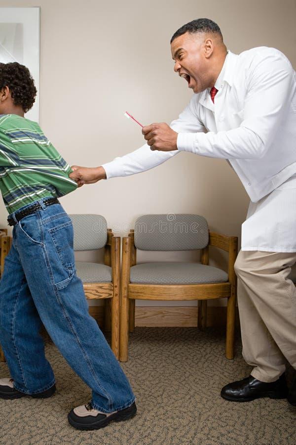 Dentista que tenta agarrar o menino fotografia de stock royalty free