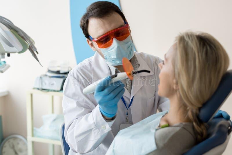 Dentista que trabalha com o cliente na cadeira fotografia de stock royalty free