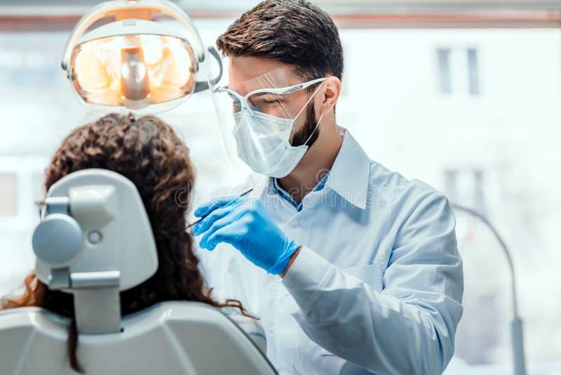 Dentista que trabalha na cl?nica dental com o paciente na cadeira fotos de stock royalty free