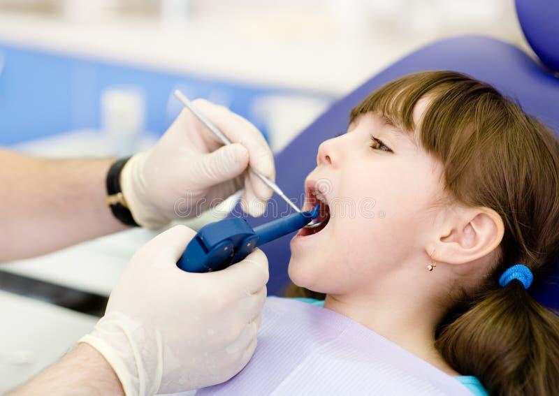 Dentista que usa el arma de relleno dental en niño imágenes de archivo libres de regalías