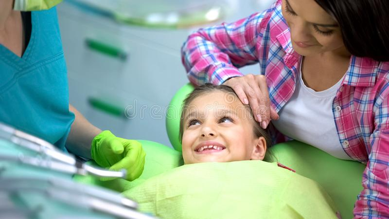 Dentista que visita sonriente de la muchacha preescolar, ningún miedo después del procedimiento, odontología de los niños foto de archivo libre de regalías