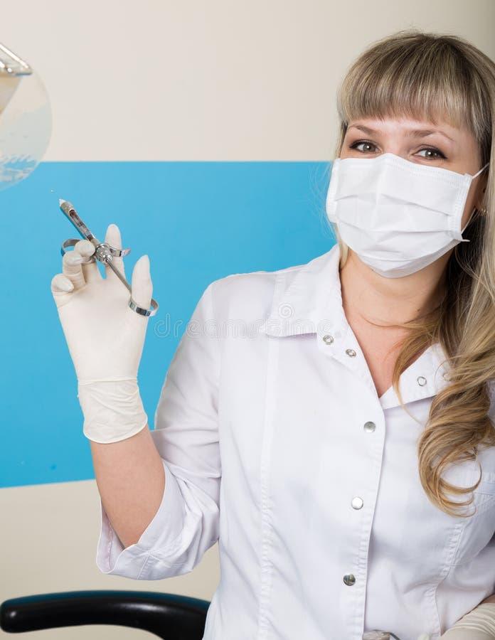 Dentista rubio de la mujer que sostiene una jeringuilla en su mano para las inyecciones imagen de archivo libre de regalías
