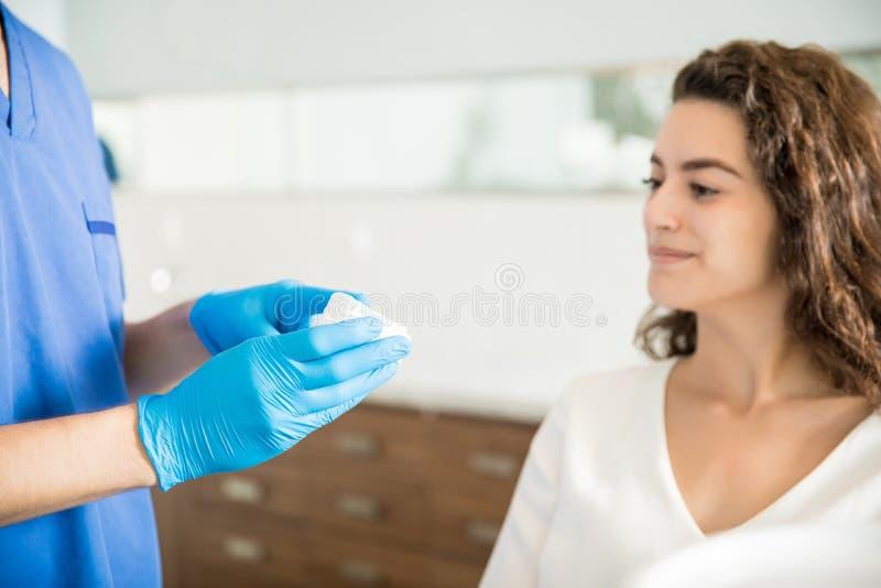 Dentista Showing Dental Mold a la mujer en clínica imagenes de archivo