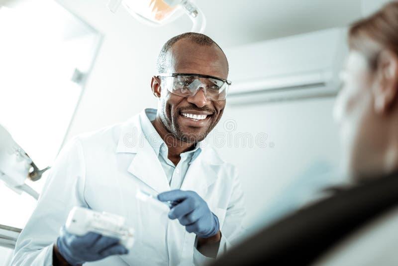Dentista sonriente hermoso que acentúa la atención en modelo del mandíbula imagenes de archivo