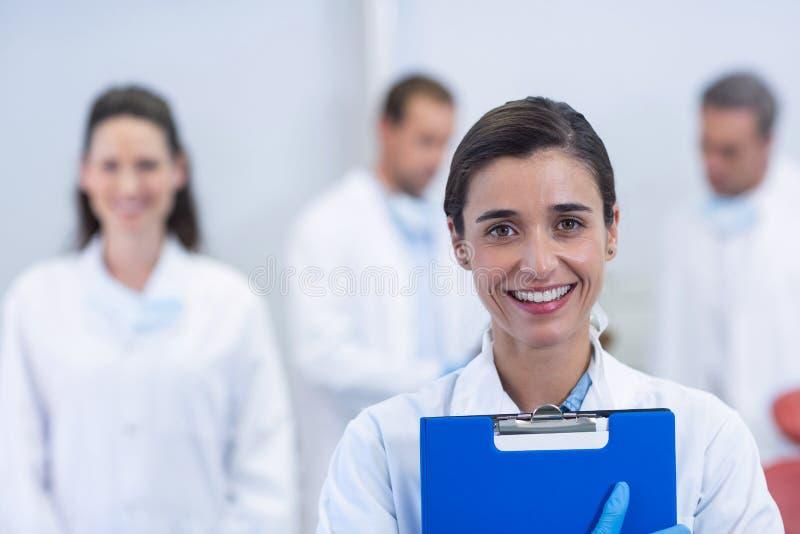 Dentista sorridente che sta alla clinica dentaria immagine stock
