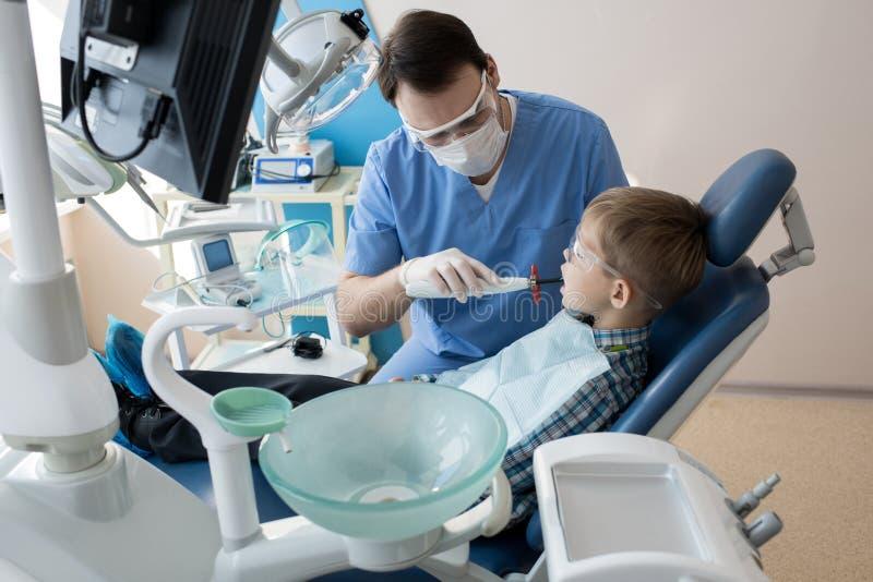 Dentista Treating Childs Teeth in clinica moderna fotografia stock