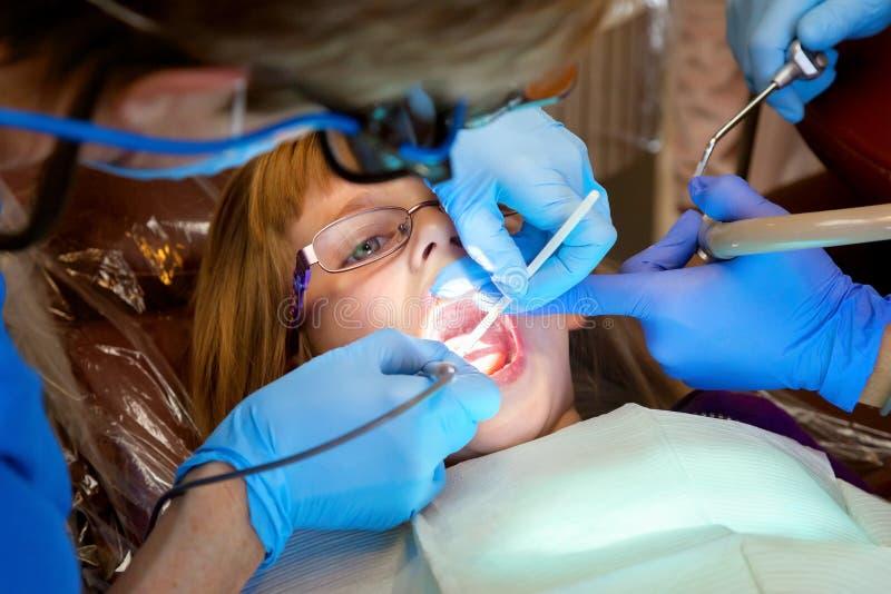 Dentista Working sui denti di una bambina fotografia stock