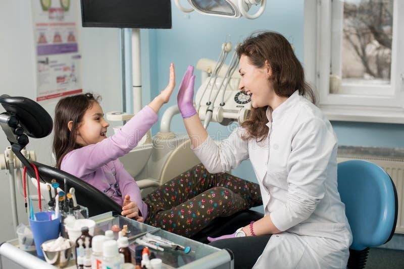 Dentista y niño precioso después de tratar los dientes en la oficina dental de la clínica, de sonreír y de dar alto-cinco Odontol imagen de archivo libre de regalías