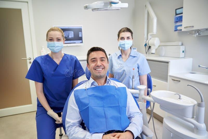 Dentistas fêmeas felizes com o paciente do homem na clínica foto de stock