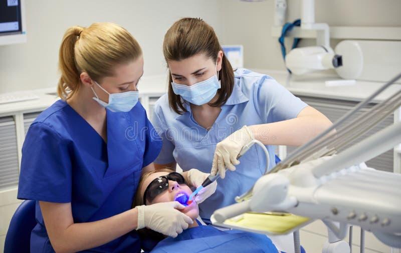Dentistas fêmeas que tratam os dentes pacientes da menina foto de stock royalty free