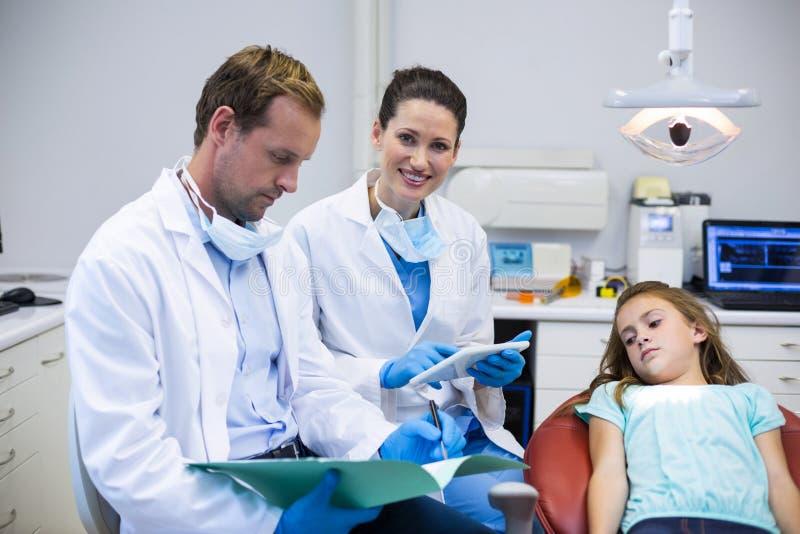 Dentistas que comprueban los informes mientras que paciente que miente en silla dental foto de archivo