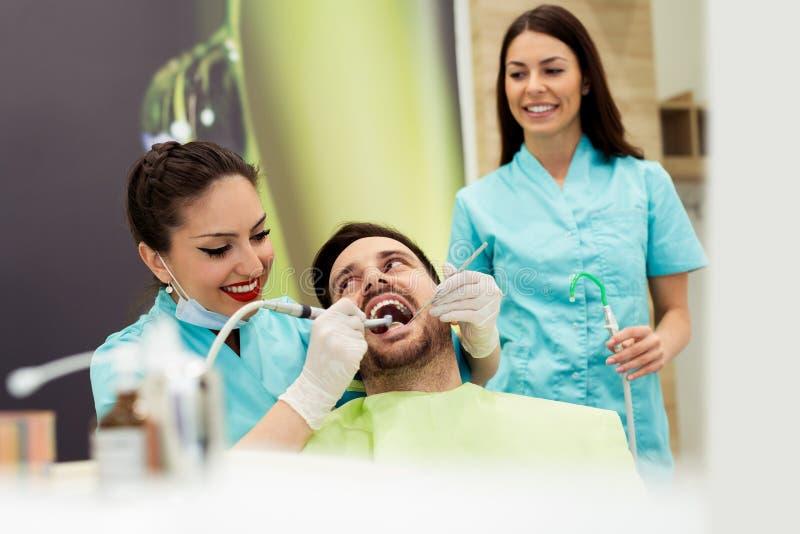 Dentistas que examinan y que trabajan en el paciente masculino Oficina del ` s del dentista fotografía de archivo