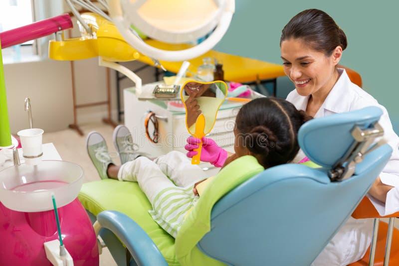 Dentiste amical de sourire de brune tenant un miroir images libres de droits