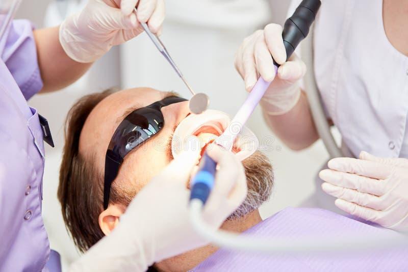 Dentiste au traitement du patient présentant la perceuse photos libres de droits