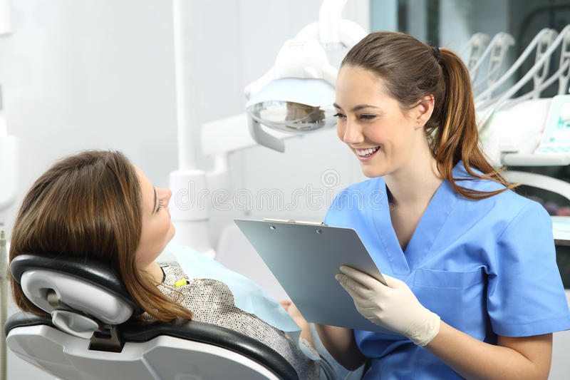 Dentiste avec des antécédents médicaux demandant à un patient photos stock